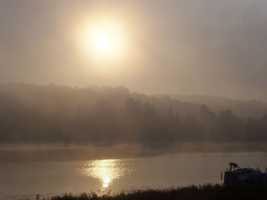 Early morning fog and sun breaking through across Hanley Lake