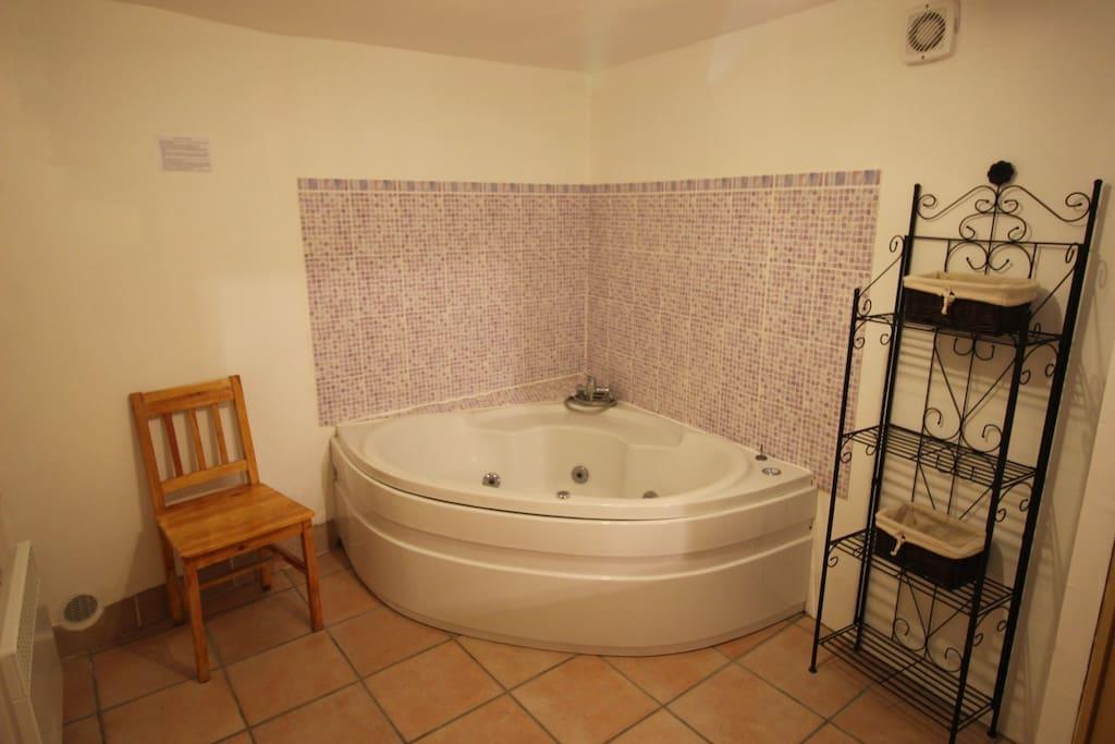Grande baignoire balnéo genre jacuzzi où il est possible de rentrer à deux