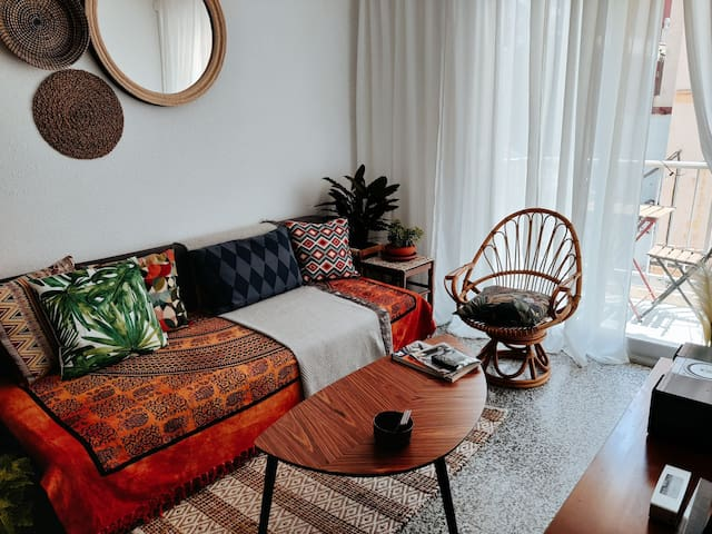 Living room with a 3-seater sofa bed, a rattan chair and access to the balcony.