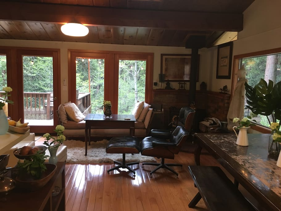 """Mid century modern high end furnishing provide a chic vibe hovering above the creek and nestled in the bosom of the wilderness. Wood fire stove in living room & an incredible view no matter where you stand or recline. Inspiration abounds. 60"""" Flatscreen TV w/ Apple TV, Netflix etc."""