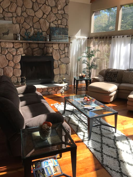 Living room boasting floor to ceiling fireplace, sectional leather sofa, soft comfortable additional sofa, large entertainment center with dvd library and more!