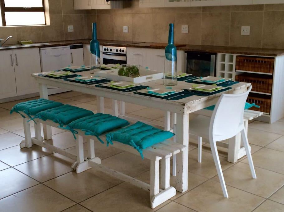Open plan kitchen equipped with dishwasher, microwave, wine fridge, fridge, washing machine and tumble dryer