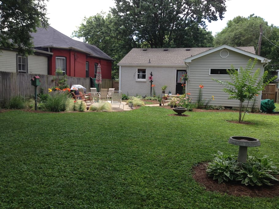 Lush landscaped  private back yard with gas grill, patio and seating.