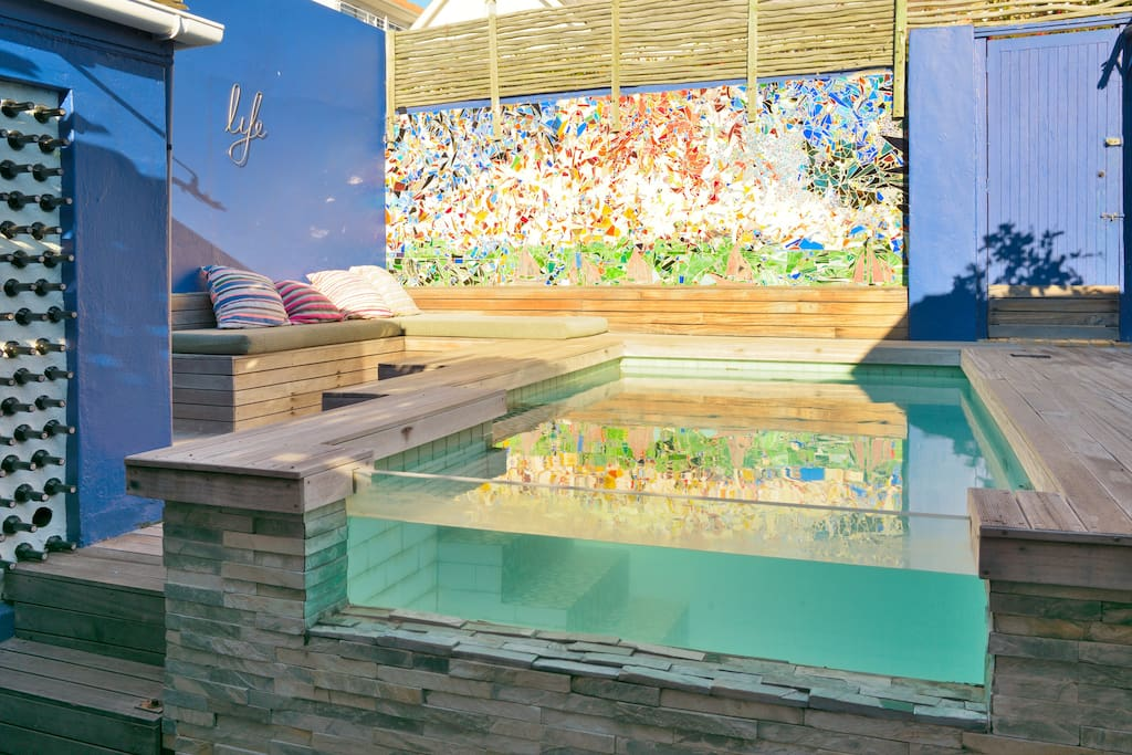 Wood, glass, water and stone are design themes that run through the house. Parents in the kitchen can monitor kids in pool, and chat with friends while whipping up snacks. From inside the pool you can see down the passage, and catch sea views beyond.