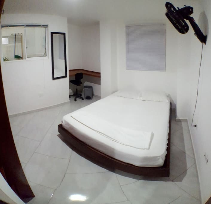1st Bedroom   Inventory: Queen Size Bed (160cm X 190cm), Wood Bed Frame, 400 Count Microfibre Bedding in White, 2 Pillows Medium Density, Large Closet Space, Custom Built Corner Workspace, Desk Chair with Wheels, Trash Can, Mirror (medium Length), Wall Mounted Air Circulating Fan, 30 Wooden Hangers