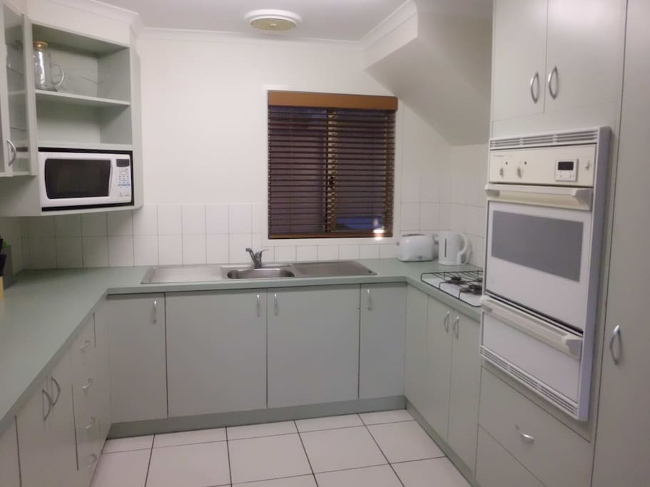 Kitchen with gas cook top, oven, grill, microwave, sink and large family fridge