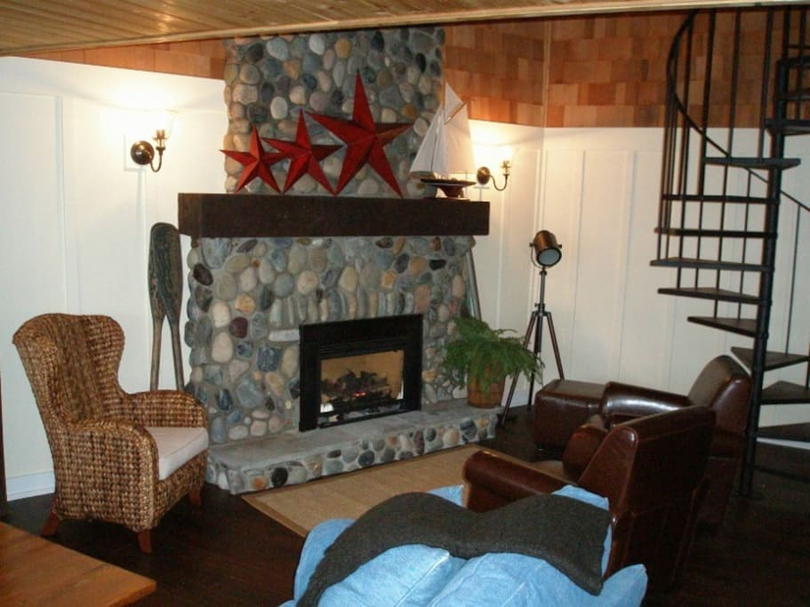 Cozy seating by the gas fireplace with hand-selected beach rock surround.