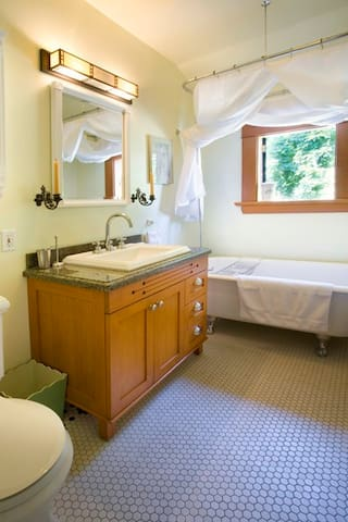 Bright bathroom with granite counter vanity, hair dryer and bath amenities.
