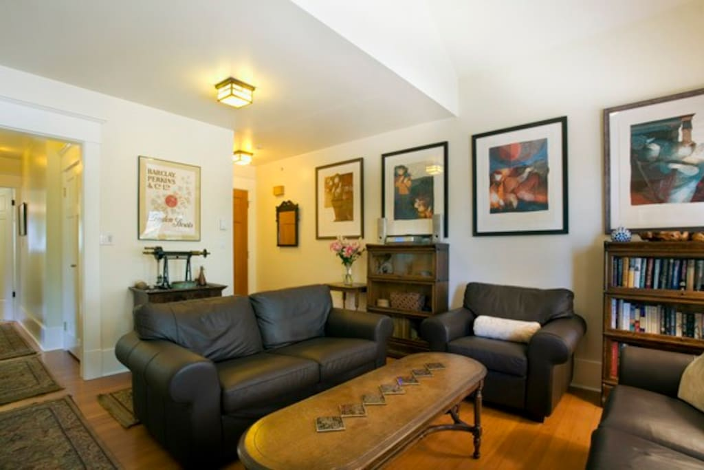 Large bright living room with hardwood floors, stained glass windows, leather couches, and tasteful décor.