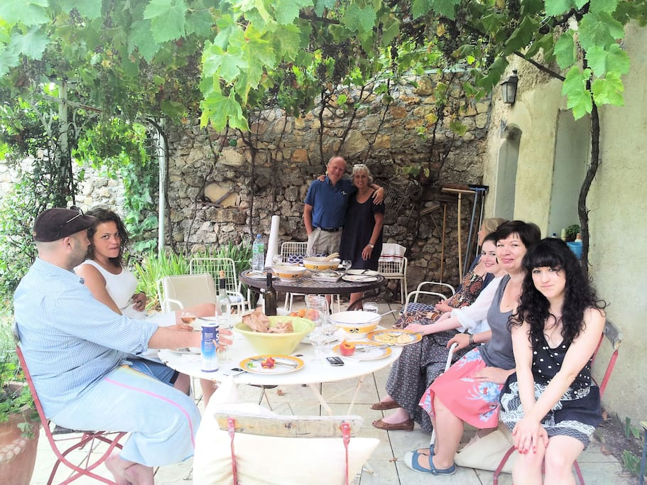 Summer eating on the terrace, shaded by vines