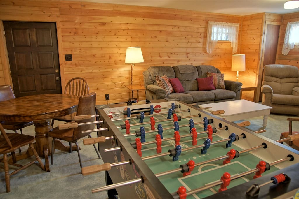 The lower living room has a Foos Ball table, game table, and lounge area