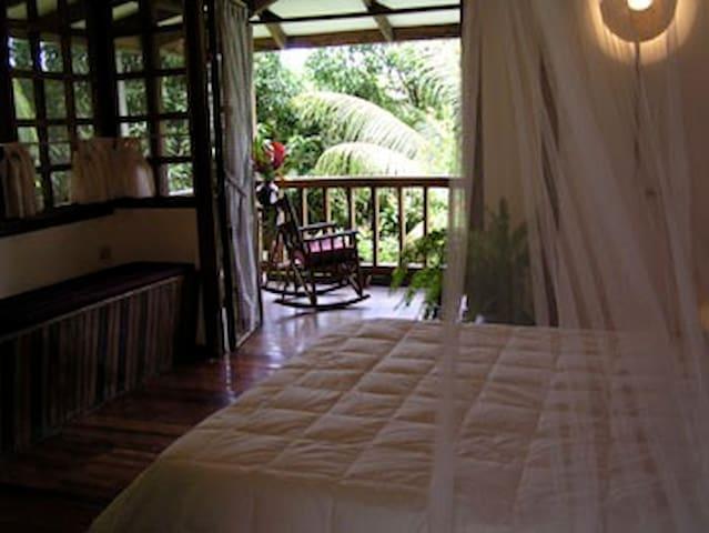 Queen bed....Bedroom looking across bed through door to veranda
