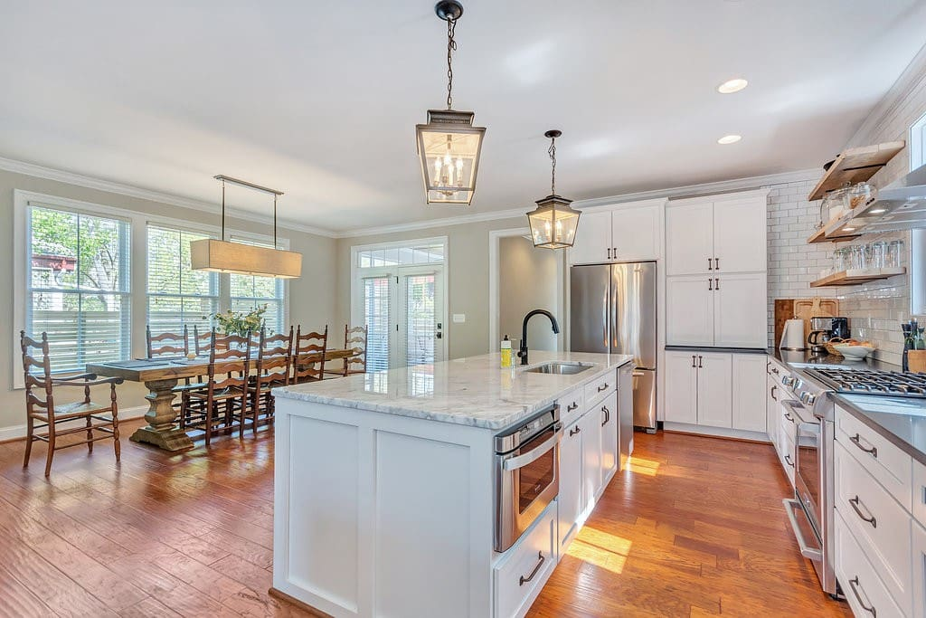 Large kitchen w/ marble island, gourmet appliances, reclaimed open shelving, open to dining area