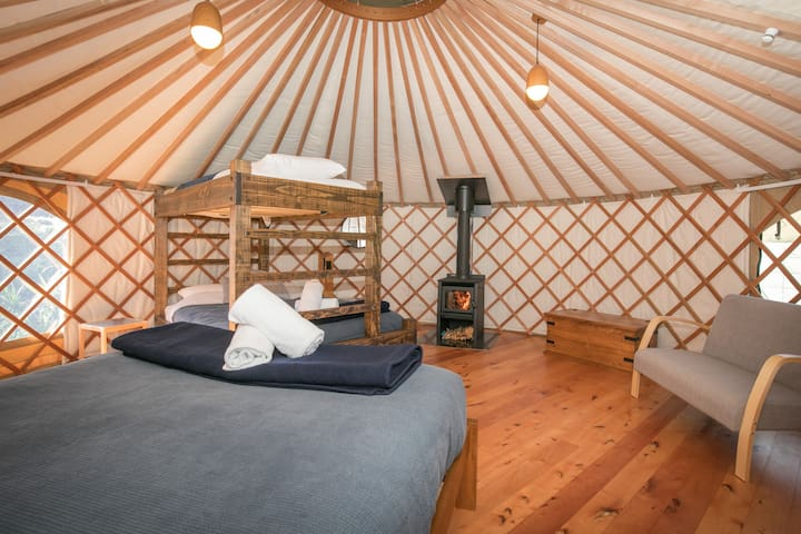 Family Yurt room interior, with comfortable NZ made mattresses, NZ wool duvets and blankets and premium linen & towels all provided.