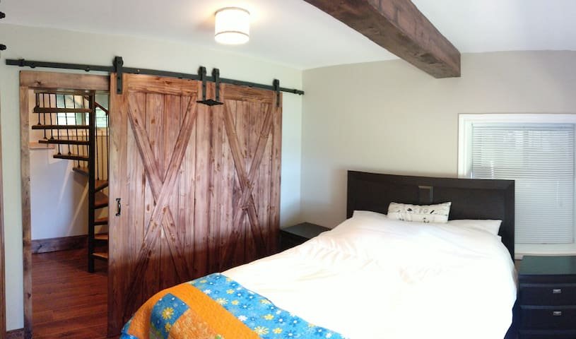 Master bedroom with queen bed, new barn doors and view of the lake