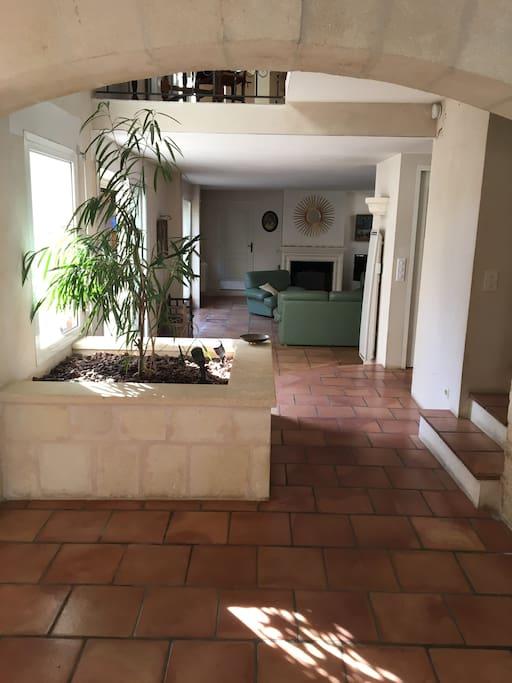 L'entrée avec vue sur la grande pièce à vivre avec cheminée