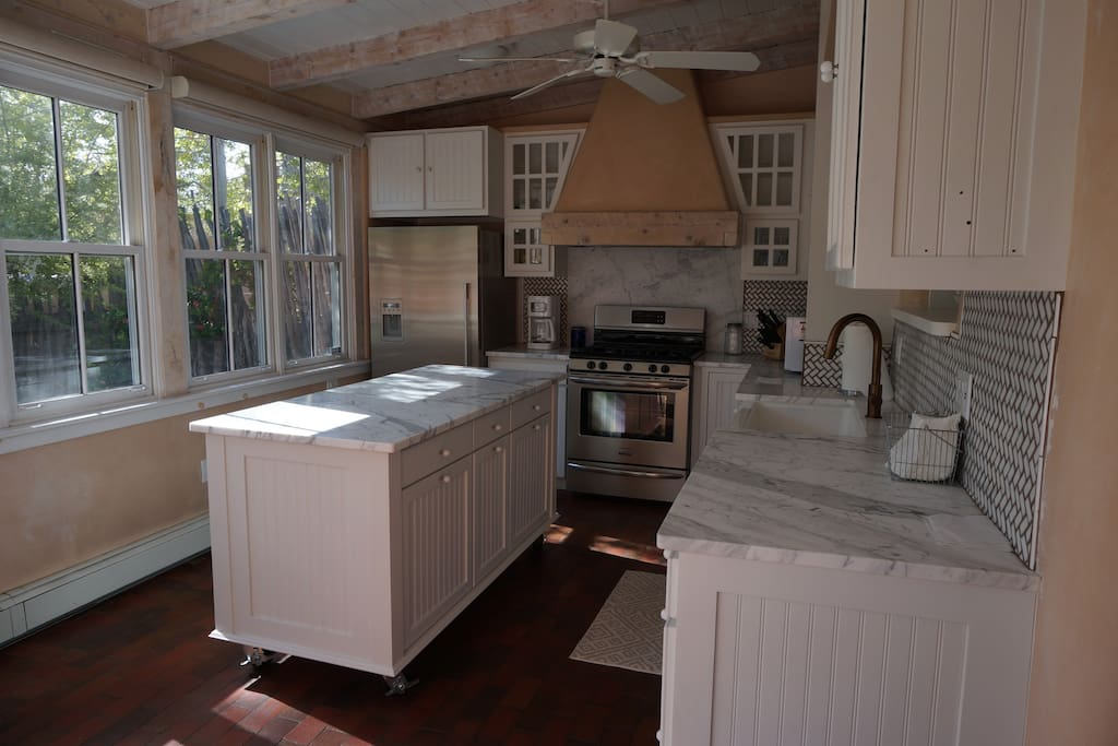 Updated, sunny kitchen with marble counters, farm sink, breakfast nook.
