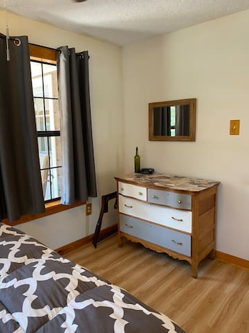 Main bedroom with dresser and mirror.