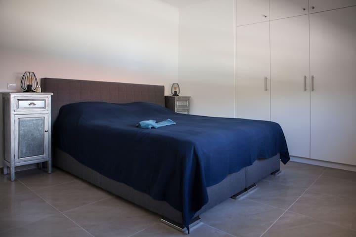 De master bedroom met de boxspring van 180x200. De stille en energie zuinig airco zorgt voor de nachtelijke verkoeling. De kamer beschikt door de ruime 4 deurs inbouwkast over veel hang en bergruimte. Vannuit de slaapkamer komt u in de badkamer