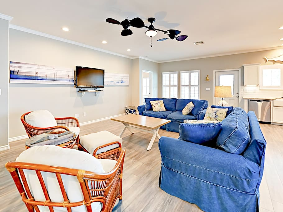 An open concept living area features plush coastal-inspired furnishings.