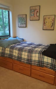 Twin bed in medium sized room. - Greenville