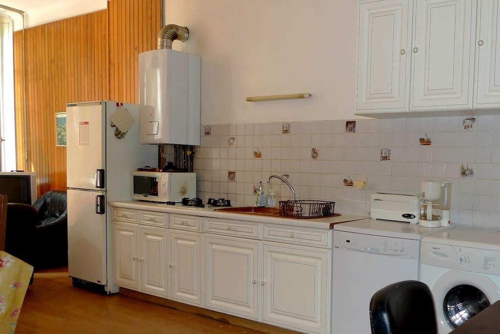 Coin cuisine dans la pièce de vie, chaudière au gaz récente, lave-vaisselle, lave-linge