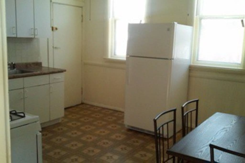 The Kitchen view with 2 windows, Refrigerator, Stove, Sink, Cabinets, Pantry, 5 piece Dining Set