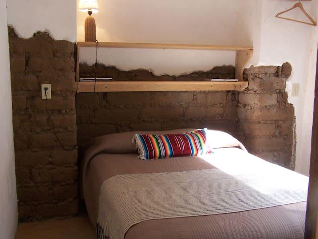 Habitación El Ciruelo. Con cama matrimonial y acceso a su baño privado. Vista sobre la montaña sagrada.