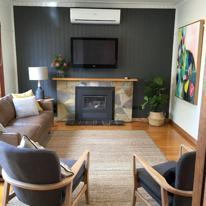 Scandi inspired lounge room with wall mounted TV, air con, gas log fire place. Cosy in winter and cool in summer. Raffs beach house has crisp white interiors and  polished floor boards throughout.