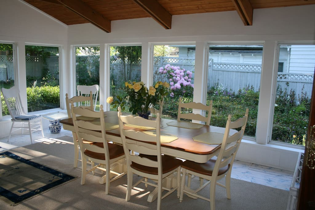 A large sunroom with vaulted ceilings, dining table and comfortable seating