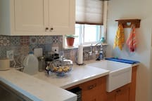 Full kitchen: farm sink, quartz countertops, fridge under counter, microwave/convection/conventional oven, dishes included, of course.