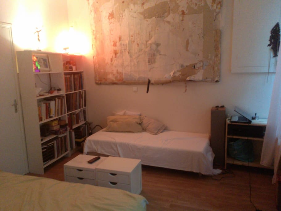 Main room with a couch/spare bed, books and soundsystem