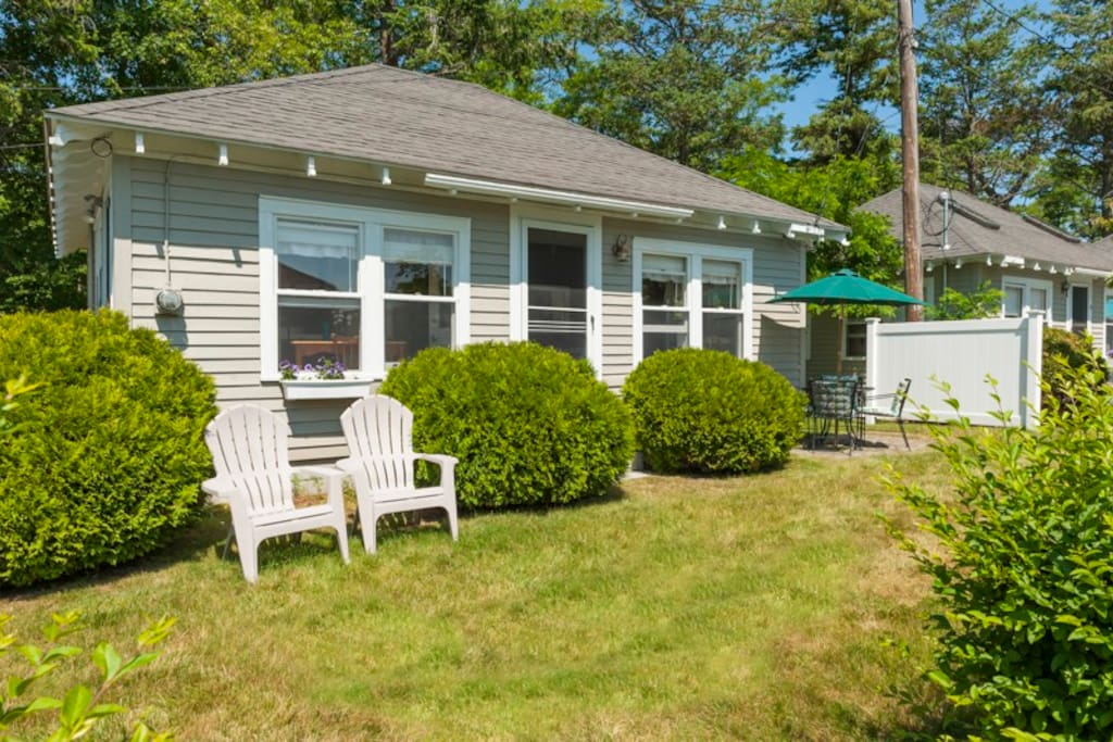 Exterior of the cottage includes adirondack chairs and a patio set