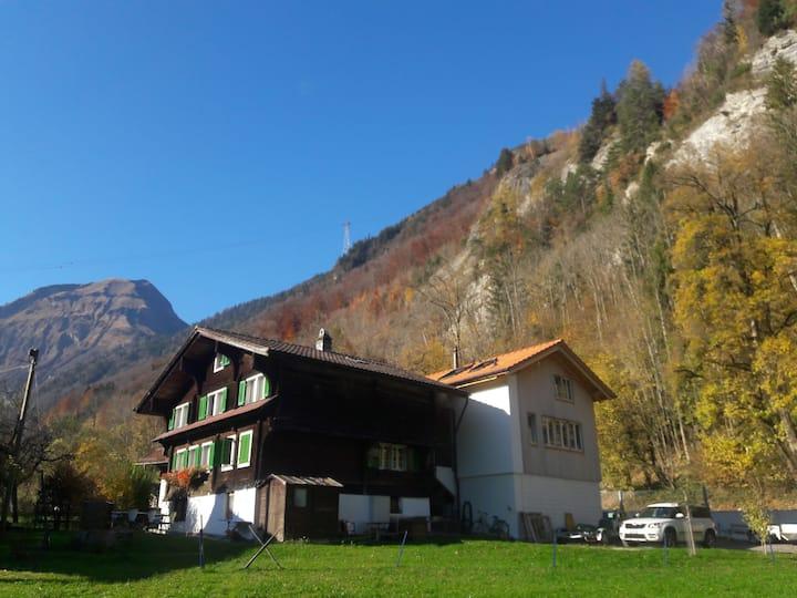 Historisches Bauernhaus neben See und Wasserfall