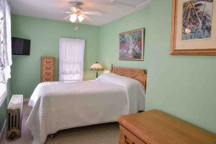 The green room has a double bed and view of the patio/pool area.