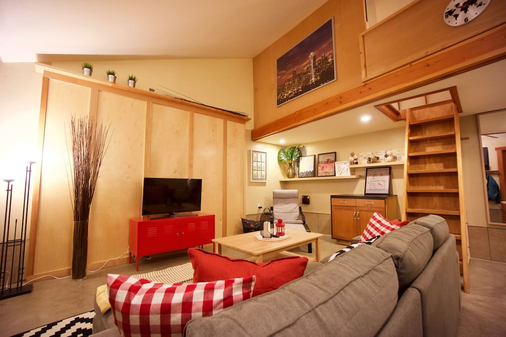 The main living area has a large sectional couch, TV and an Apple TV with DirecTV service, along with a reading chair.