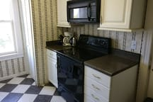 Fully stocked kitchen with microwave, oven, fridge, toaster, blender, coffee maker, and more