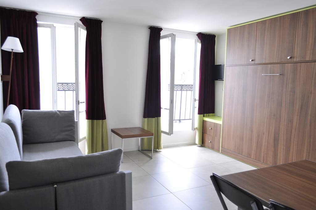 Living room equipped with flippable double bed, sofa bed and dining table