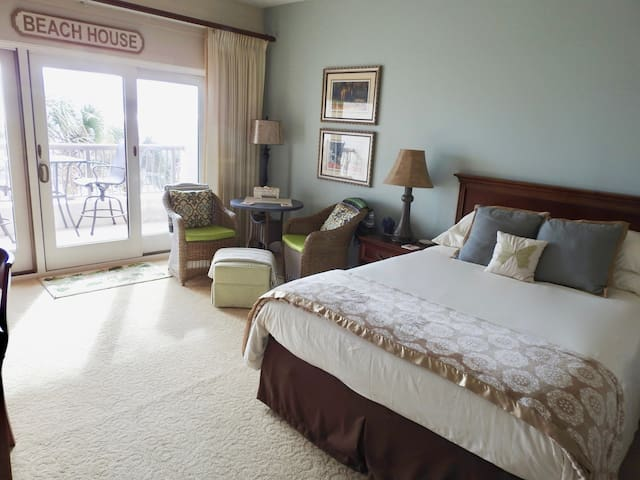 """Queen size bed, sitting area and private balcony overlooking pool, dunes and ocean. """"A great view of the ocean from the apartment. Everything you need is there. Very comfy bed too!"""""""