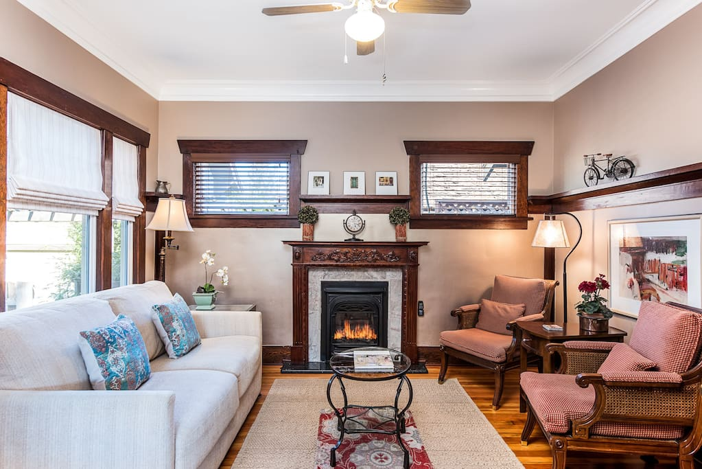 Intimate Living space with ample seating  graced with a carved cherry mantel and fireplace as a center piece