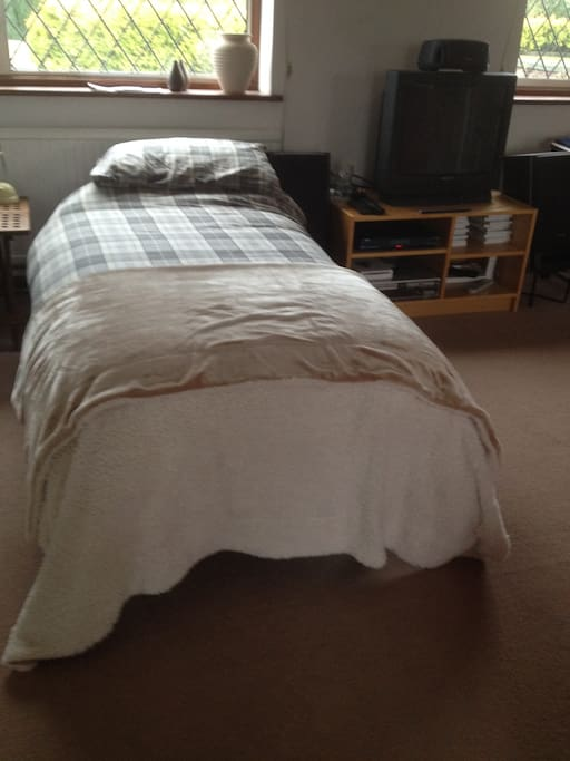 Single bed with bedside table and TV to watch from under the covers. Views of Ivinghoe Beacon from this end of the room.