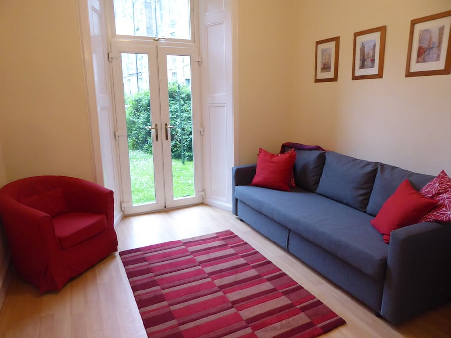 Livingroom with sofa bed and French doors leading to garden