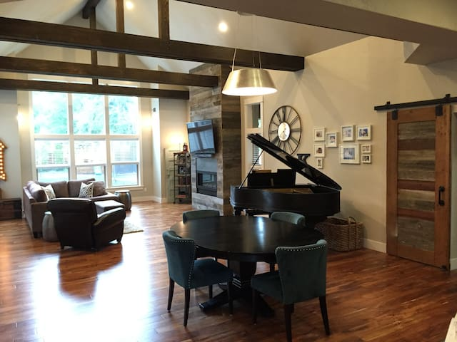 """Extremely large family room with  cathedral ceilings, grand piano, 60"""" flatscreen, dining area and open floorplan to adjacent kitchen"""