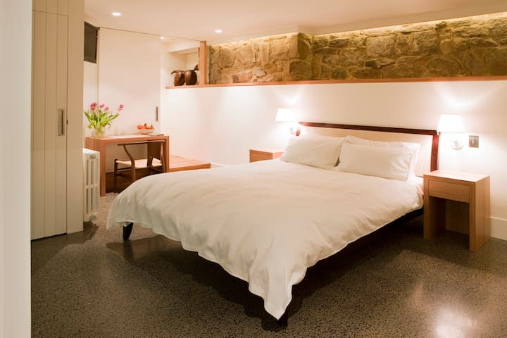 Downstairs double bedroom with sandstone wall and concrete heated floor