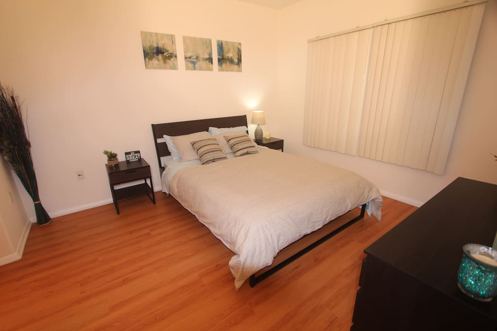 Queen size bed in a very cozy bedroom.