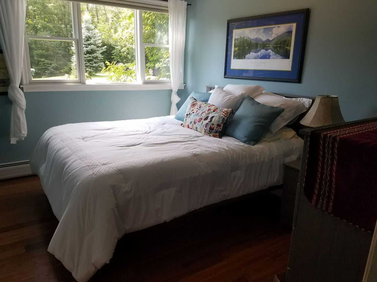 Queen size bed, lots of pillows, picture window with a view of the front yard.