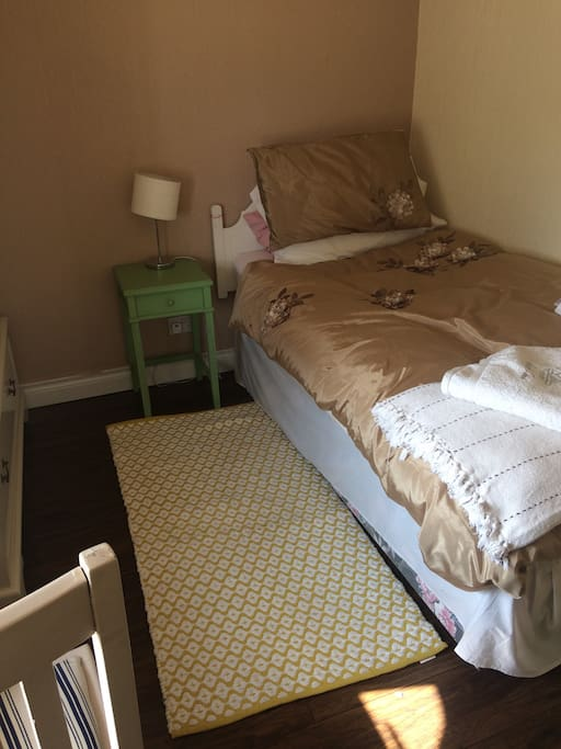 The Bedroom. Single bed with white headboard . Green bedside cabinet with reading light .. bedside soft rug
