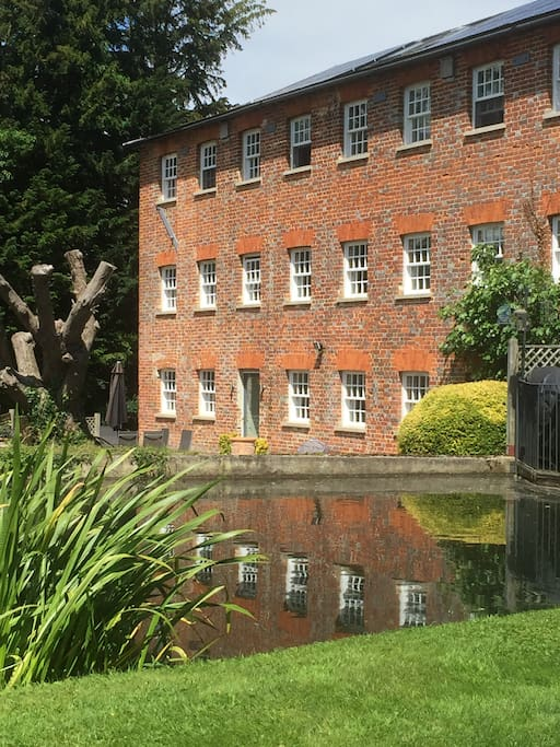 The exterior of the Mill, reflected in the tranquil water that runs alongside