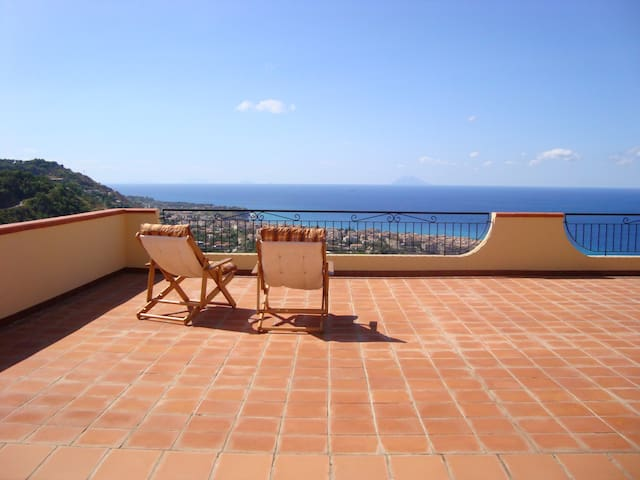 Panoramic ocean view over Tropea from sunloungers on terrace