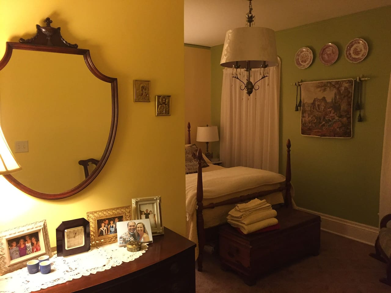 The Yellow Room features a comfortable full size bed in an antique bedroom set, a TV with full digital channels and premium movie options, and an upholstered rocking chair.